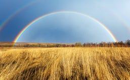 Ovannämnt lantgårdfält för härlig full regnbåge på våren fotografering för bildbyråer