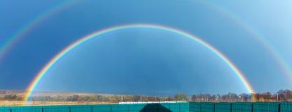 Ovannämnt lantgårdfält för härlig full regnbåge på våren arkivbilder