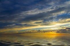Ovannämnt lugna vatten för oerhörd solnedgång Arkivbild