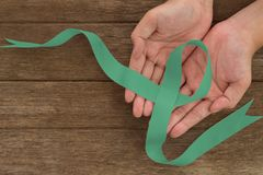 Ovarian cancer and gynecological disorders concept. Green ribbon symbolic support campaign on people living life with Ovarian cancer royalty free stock photo