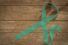 Ovarian cancer and gynecological disorders concept. Green ribbon symbolic support campaign on people living life with Ovarian cancer stock images