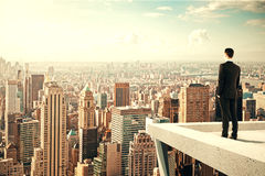 站立在摩天大楼的屋顶和看ove的商人 免版税图库摄影