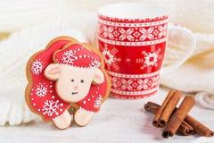 Ovejas rojas del pan de jengibre de la Navidad con la taza de leche Imagenes de archivo