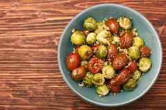 Oven baked brussels sprouts and tomatoes with pistachios Royalty Free Stock Images