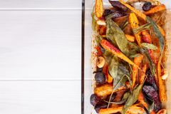 Oven baked carrots and beetroots with sage leaves and garlic royalty free stock image