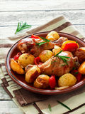 Oven-baked chicken drumsticks and potatoes Stock Photo