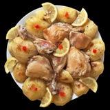 Oven Baked Chicken Legs avec des tranches de pomme de terre et de citron du plat de porcelaine d'isolement sur le fond noir Image libre de droits