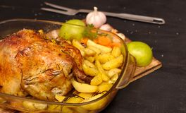 oven-baked crispy crust stuffed chicken on a plate with potatoes, apples, garlic royalty free stock photography