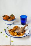 Oven baked Duck leg with fried persimmons. On a white table stock photo
