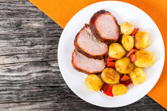 Oven Baked new potatoes with pork chop stock photo