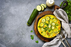 Oven baked omelette with zucchini in a cast iron pan.Top view wi. Oven baked omelette with zucchini in a cast iron pan over dark grey slate,stone or concrete Royalty Free Stock Photo