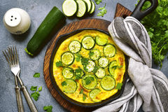 Oven baked omelette with zucchini in a cast iron pan.Top view wi. Oven baked omelette with zucchini in a cast iron pan over dark grey slate,stone or concrete Stock Image