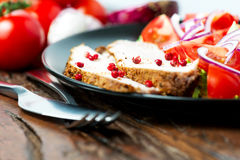 Oven baked pork in plate with salad and ingredients Stock Image