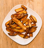 Oven baked potato chips on a white plate Stock Images