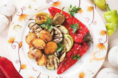 Oven baked potato and grilled vegetables. Oven baked spicy potato with grilled vegetables, healthy vegetarian dish Stock Photos