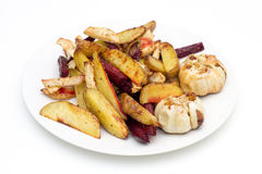 Oven baked potatoes, beetroot, celeriac and garlic royalty free stock photo