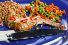 Oven baked rabbit leg. S with green peas and carrot Stock Photos