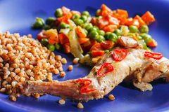Oven baked rabbit legs. With green peas and carrot Stock Photos