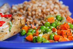 Oven baked rabbit legs. With green peas and carrot Royalty Free Stock Photography