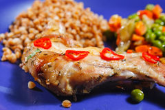 Oven baked rabbit legs. With green peas and carrot Stock Image