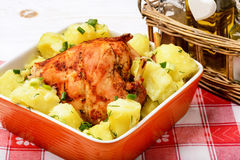 Oven baked rabbit with potatoes  in orange ceramic bowl . Oven baked rabbit with potatoes  in orange ceramic bowl on white  wooden table Royalty Free Stock Photo