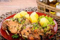 Oven baked rabbit with potatoes on red plate on wooden table. Royalty Free Stock Photography
