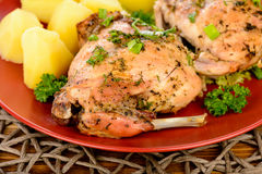 Oven baked rabbit with potatoes on red plate on wooden table. Royalty Free Stock Images