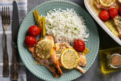 Oven baked salmon with leek and tomatoes, served with boiled rice. royalty free stock photo