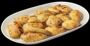 Oven Baked Seasoned Potato Halves na bandeja oblonga branca da porcelana no fundo preto foto de stock royalty free