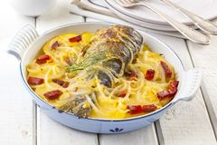 Oven baked trout. Delicious oven baked trout with potatoes, onions and ham stock image