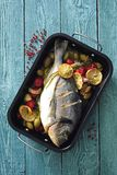 Oven baked whole sea fish with green olives, cherry tomatoes, lemon and herb butter. In black baking tin there is oven baked whole sea fish with green olives Stock Images