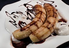 Oven Bananas with chocolate. On white plate, isolated on black Stock Image