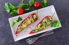 Oven cooked red paprika stuffed with cheese, garlic and herbs on a white plate with parcley and cherry tomatoes an Stock Image