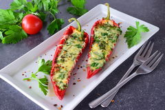 Oven cooked red paprika stuffed with cheese, garlic and herbs on a white plate with parcley and cherry tomatoes an Stock Photos