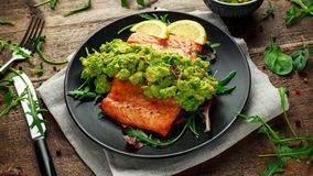 Oven cooked salmon steak, fillet with avocado salsa and green on black plate. wooden table. healthy food.  Stock Photos