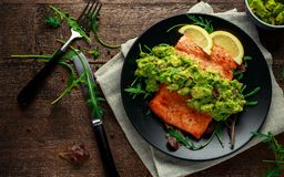 Oven cooked salmon steak, fillet with avocado salsa and green on black plate. wooden table. healthy food.  Royalty Free Stock Image