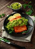 Oven cooked salmon steak, fillet with avocado salsa and green on black plate. wooden table. healthy food.  Stock Images