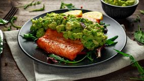 Oven cooked salmon steak, fillet with avocado salsa and green on black plate. wooden table. healthy food.  Royalty Free Stock Images
