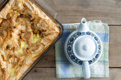 Oven dish with plain Turkish borek and a teapot Stock Image