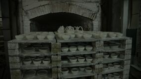 Oven for firing dishes. A rack of baked earthenware is rolled out of the oven. Subjectively. The view from the top. General plan.