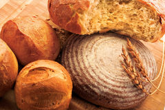 Oven-fresh loaf. A close-up of a new-baked loaf of bread with a wheat head Royalty Free Stock Photography