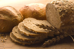 Oven-fresh loaf. A close-up of a new-baked loaf of bread with a wheat head Stock Photos