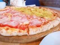 Oven Ham Pizza. Homemade pizza served on a stone serving dish.  royalty free stock image