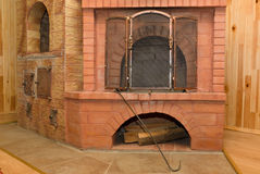 Oven in the house. It is located the oven from a red brick in the house and serves for heating Royalty Free Stock Images