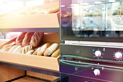 Oven and loaves of bread on shelf. Oven and loaves of bread on a shelf in a bakery stock photos