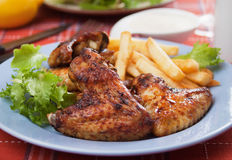 Oven roasted chicken wings. With french fries  and lettuce Royalty Free Stock Images
