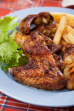Oven roasted chicken wings. With french fries  and lettuce Royalty Free Stock Image