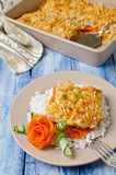 Oven-roasted fish fillet with carrots under a bread crust Stock Photos