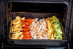 Oven Roasted Potatoes, Green Bean, Bell Pepper and Sausage, seasoned with spring onion and pieces of chili on a baking sheet, clos stock image