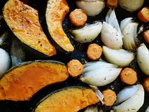 Oven roasted vegetables on black tray. Oven roasted orange pumpkin, orange carrots and white onion on black tray royalty free stock photography